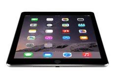 有角度的正面图与iOS 8的苹果计算机空间灰色iPad空气2说谎 免版税图库摄影