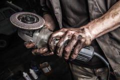 有角度研磨机的肮脏的手 库存照片