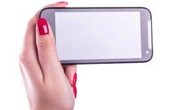 有触摸屏幕的手机在有法式修剪钉子的女性手上在白色 免版税库存图片