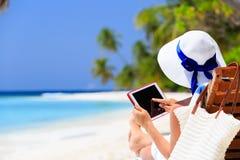 有触摸板的妇女在热带海滩 免版税库存图片