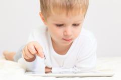 有触摸板的,早期的教育小男孩 免版税库存图片