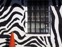 有警告安全锥体的笼中的窗口斑马镶边墙壁 免版税库存图片