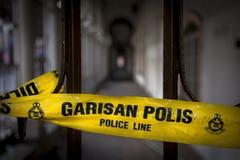 有警察线字词的黄色磁带在英语和马来的语言不横渡 库存照片