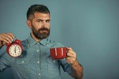 有警报的,完善的早晨红色杯子 人用被仔细考虑的酒,在蓝色背景的时钟 免版税库存图片