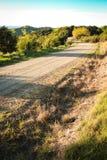 有警棒和铁丝网的, Mahia半岛,北岛,新西兰被金属化的农村路 免版税图库摄影