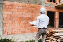 有计划的建筑工程师,运作在大厦工地工作 砖墙,在工地工作的基础设施 免版税库存图片