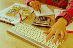 有计算器、笔、笔记和钞票的女性在一张木桌上 免版税库存图片