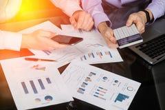 有计算器和电话的人的手在本文的背景在桌上的 免版税库存照片