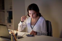 有计算器和纸的妇女在夜办公室 免版税库存照片