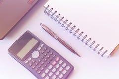 有计算器和膝上型计算机的,笔,在白色桌背景的笔记本运转的书桌 到达天空的企业概念金黄回归键所有权 图库摄影