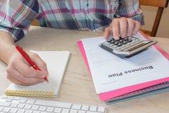 有计算器的人手在工作场所办公室 做一些文书工作的商人使用他的计算器 免版税库存图片