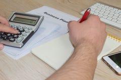 有计算器的人手在工作场所办公室 做一些文书工作的商人使用他的计算器 免版税库存照片