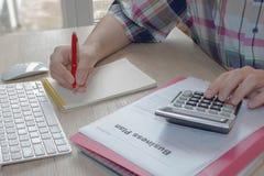 有计算器的人手在工作场所办公室 做一些文书工作的商人使用他的计算器 免版税图库摄影