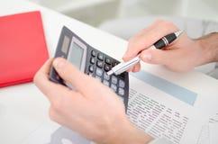 有计算器的商人的手 免版税库存图片