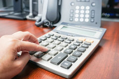 有计算器的女会计在IP电话 免版税库存照片