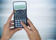 有计算器的手反对模糊的蓝色木盘区 免版税库存照片