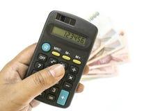 有计算器的手和在白色背景的泰国钞票 免版税库存图片