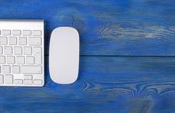 有计算机、无线键盘和老鼠的企业工作场所在老红色木桌背景 有拷贝空间的办公桌 库存照片