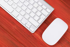 有计算机、无线键盘和老鼠的企业工作场所在老红色木桌背景 有拷贝空间的办公桌 库存图片