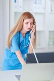 有计算机和电话的医生妇女 免版税库存照片
