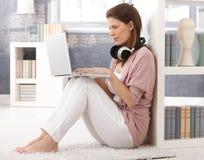 有计算机和耳机的俏丽的妇女在家 免版税库存照片