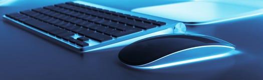 有计算机无线键盘和老鼠的企业工作场所在老蓝色桌背景 有拷贝空间的办公桌 库存照片