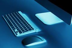 有计算机无线键盘和老鼠的企业工作场所在老蓝色桌背景 有拷贝空间的办公桌 免版税库存图片