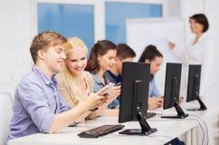 有计算机显示器和智能手机的学生 免版税库存照片