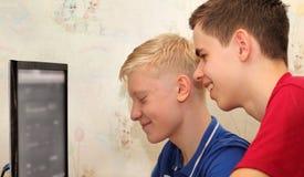有计算机显示器的少年在家 免版税库存照片