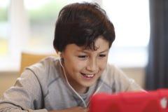 有计算机片剂的男孩 库存图片