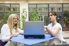 有计算机的两名女实业家 免版税图库摄影