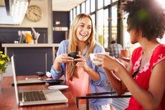有计算机的两名妇女笑在咖啡店的 图库摄影