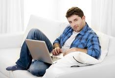 有计算机的可爱的人坐长沙发 库存图片