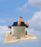 有计算机的商人在魔术地毯乘驾 免版税库存照片