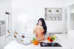 有计算机的妇女在厨房里 库存照片
