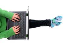 有计算机的学生在膝部 免版税图库摄影
