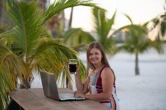 有计算机的年轻女人在棕榈前面 免版税库存照片
