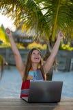 有计算机的年轻女人在棕榈前面 免版税库存图片