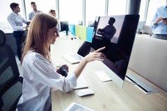 有计算机的年轻女商人在办公室 免版税库存照片