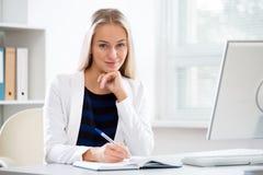 有计算机的年轻美丽的女商人 库存照片