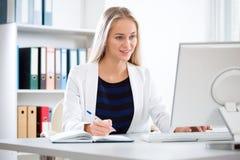 有计算机的年轻美丽的女商人 免版税库存照片