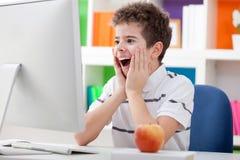有计算机的惊奇的男孩 图库摄影
