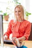 有计算机的愉快的女商人在办公室 免版税库存图片