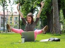有计算机的愉快的妇女在都市公园 免版税库存图片