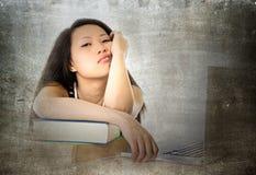 有计算机的年轻人相当中国亚裔学生妇女使疲乏和劳累过度倾斜在教科书学习不耐烦 免版税库存图片