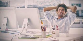 有计算机的轻松的偶然商人在明亮的办公室 免版税库存图片