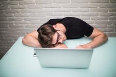 有计算机的年轻英俊的人在办公室认为在编程的睡觉的任务的在工作表 图库摄影