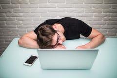 有计算机的年轻英俊的人在办公室认为在编程的睡觉的任务的在工作表 免版税库存照片