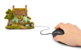 有计算机老鼠和房子的手 免版税库存图片
