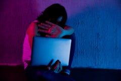 有计算机膝上型计算机在网上被滥用的痛苦cyberbullying和骚扰的哀伤和害怕的女性少年  免版税库存照片